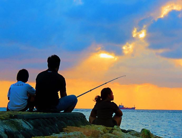 一位印尼父亲带着他的一对儿女在海边垂钓
