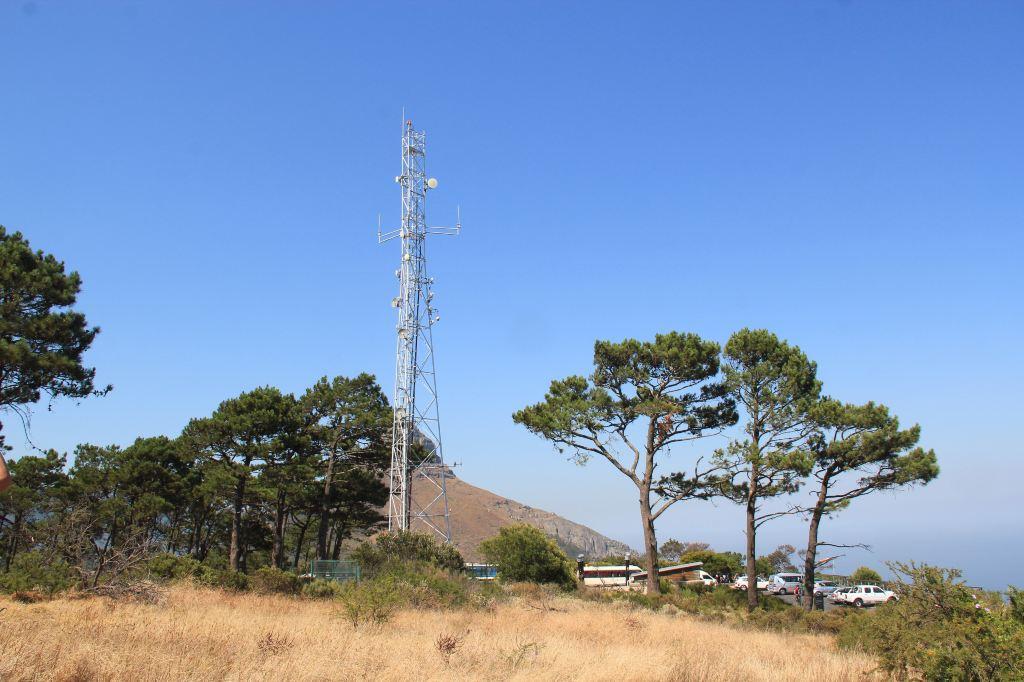 南非游第9天,酒店早餐後乘車去信號山,汽車沿盤山公路可直接上山。 信號山位于桌山一側,同屬桌山國家公園景區,海拔350米。人們曾在山頂升旗為進入海灣的船只打信號,故名為信號山,現每天正午仍有信號炮發射。 我們從信號山左邊的小路往上走,山頂很平坦,上面長了許多毛草以及樹木,還有信號塔。轉了一圈,感覺信號山不大,本身沒有什麼風景。但在信號山山頂既可以從最佳角度欣賞到桌山,又可看到漂亮的大西洋海岸線,還可俯瞰開普敦繁華都市和綠點球場等。 在信號山上有一個大大的像框,背景是著名的桌山,框邊標有地理位置,游人一般
