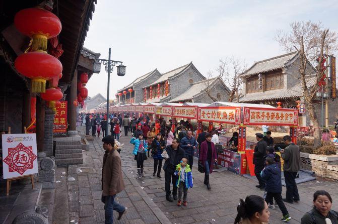 旁边的高家亭巷正在举办青州古城新春美食节,展现了青州饮食文化.