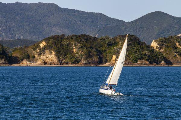 湾里迎风的白帆,远处山峦层叠,风景极为优美.